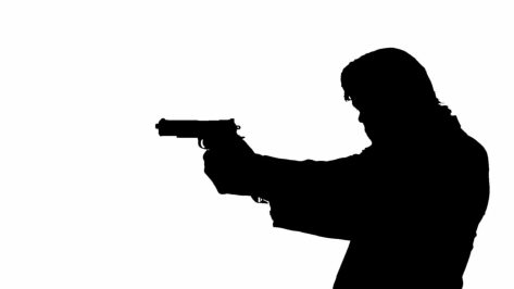 stock-footage-silhouette-of-a-man-with-a-gun-walking-and-aiming-down-the-sights-of-his-pistol-he-could-be-a-hit